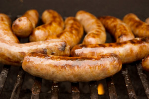 Bratwurst sausages grilling on a barbeque.